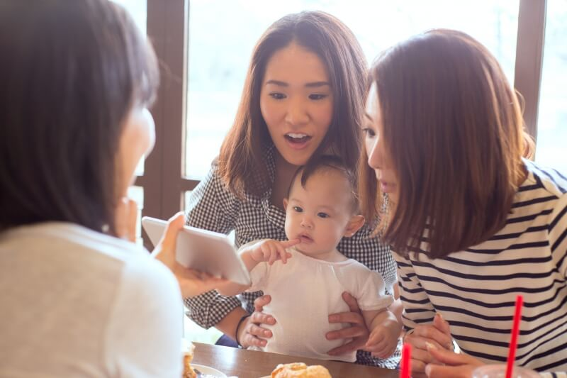 Baby bonus and insurance – 3 Asian women and a baby looking at a mobile phone