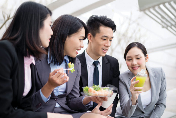 People in office attire having lunch
