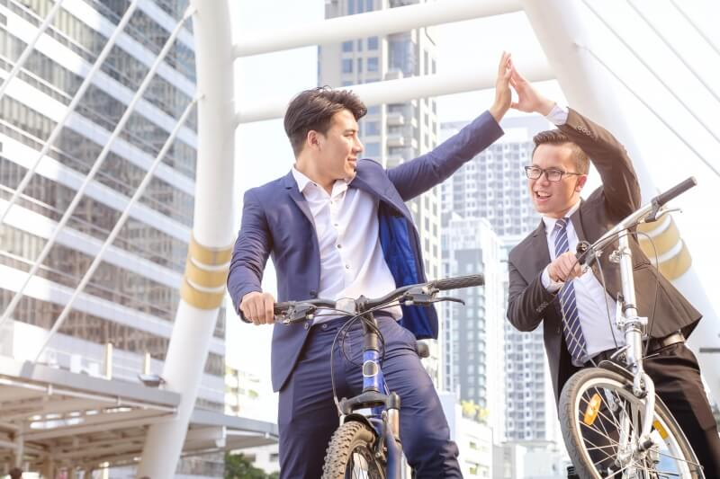 Job interview tips to ace interview – two young men in suits riding a bike