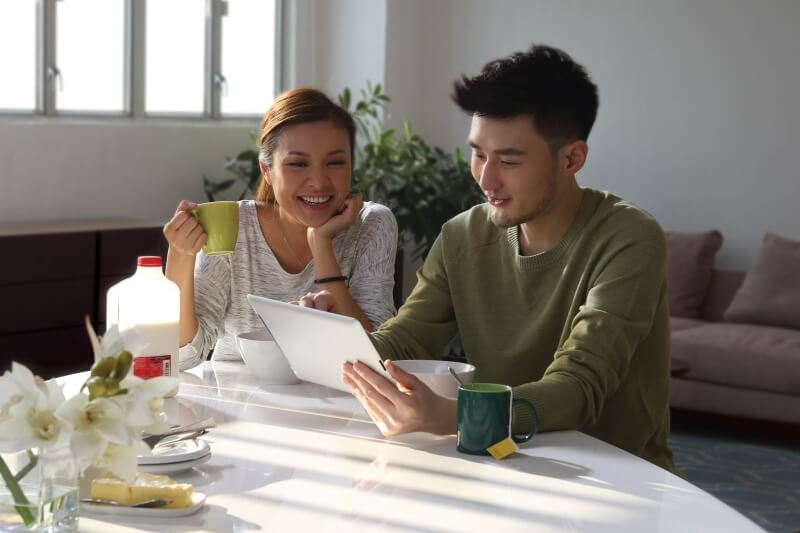 Importance of Life Insurance – happy Asian couple using iPad at breakfast table